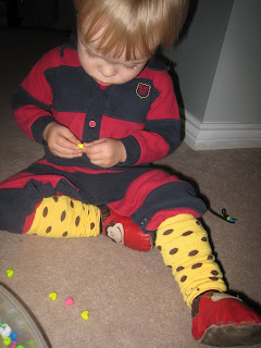 Maximilian putting beads on shoelaces