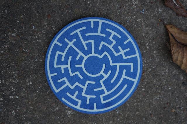 closeup of blue and white resin cast maze coaster