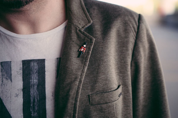 Quinton VanMeter wearing Union Jack tee, olive blazer, and london palace guard lapel pin