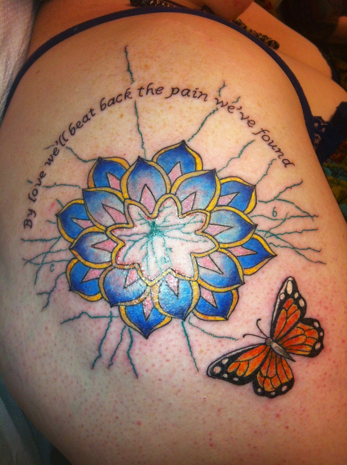 "Photograph: A close-up of a fresh tattoo. On the top are the words ""By love we'll beat back the pain we've found."" The center is a stylized lotus flower in blue and pink, outlined in yellow. Behind the lotus is a linework drawing of a neuron in green. On the bottom is an orange monarch butterfly."