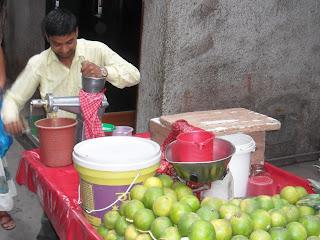 индус выжимает апельсиновый сок