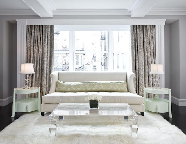 Living room with lucite coffee table, pale green side tables, white sofa with long bolster, dark wood floor, fur rug and floor length curtains
