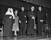 Bishop Charles Helmsing and others on the stage at Notre Dame High School