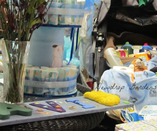 Diaper cake surrounded by baby shower gifts