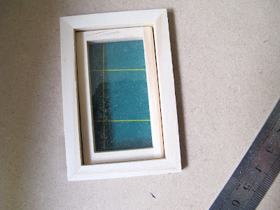 Dolls' house window inserted into a hole cut in a sheet of MDF.