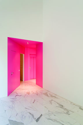 White room and pink door of The L House by Philippe Stuebi Architekten GMBH