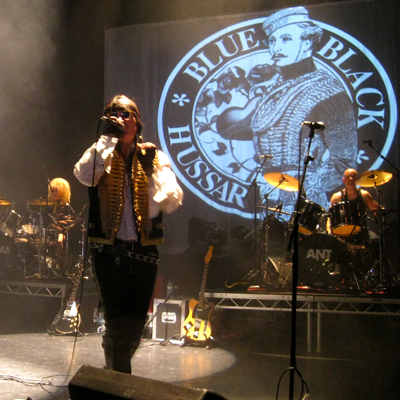 Adam Ant and drummers Jola and Dave Barbarossa with the Blue Black Hussar logo in concert, Hammersmith Apollo, London 19apr2014.