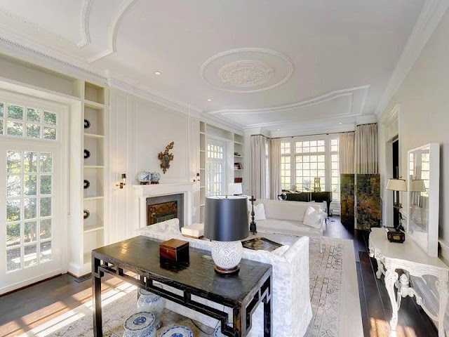 White living room with French doors and windows, wood floors, fireplace, dueling sofa and paneled ceiling