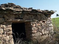 Detall de la porta amb la llinda i el ràfec per escopir la pluja a la barraca nº 5