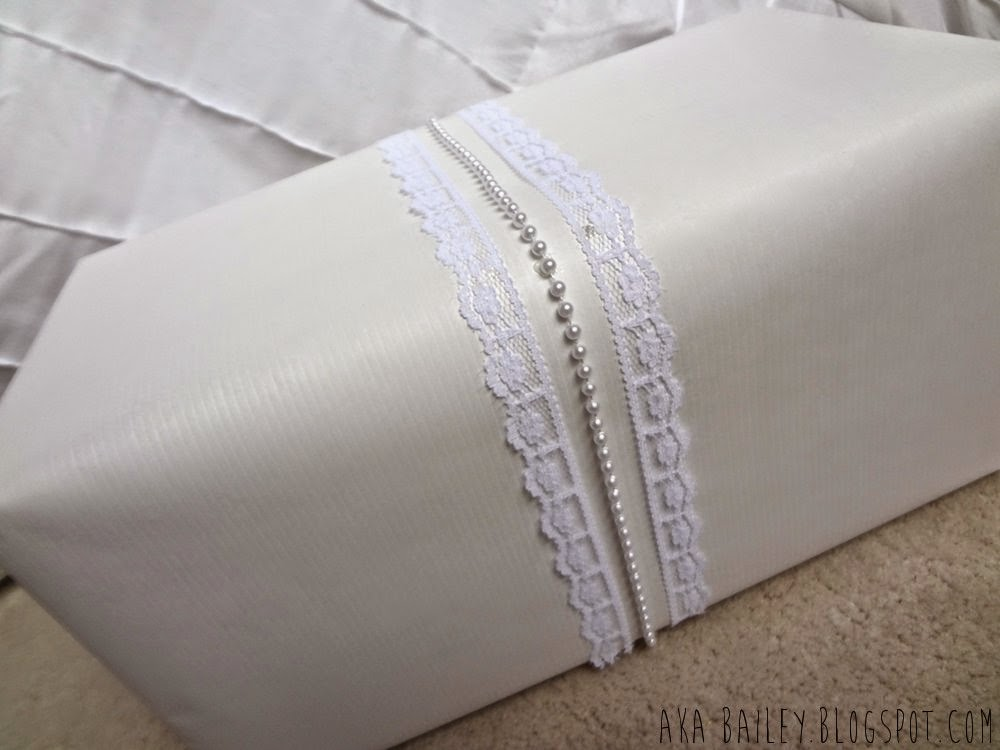 White paper gift wrap with white lace and pearls