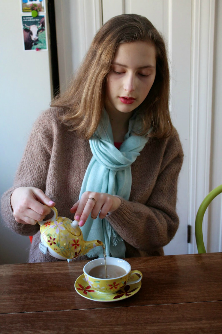 Caramel colored sweater, drinking tea with red lipstick