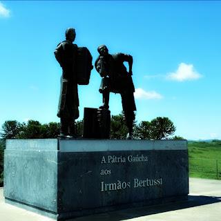 Memorial dos Irmãos Bertussi: o da esquerda tocando acordeão. O da direita com o pé sobre o acordeão.