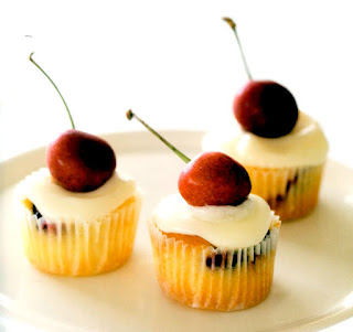 Mini cupcakes with cherries in the batter that are served garnished with a whole cherry.