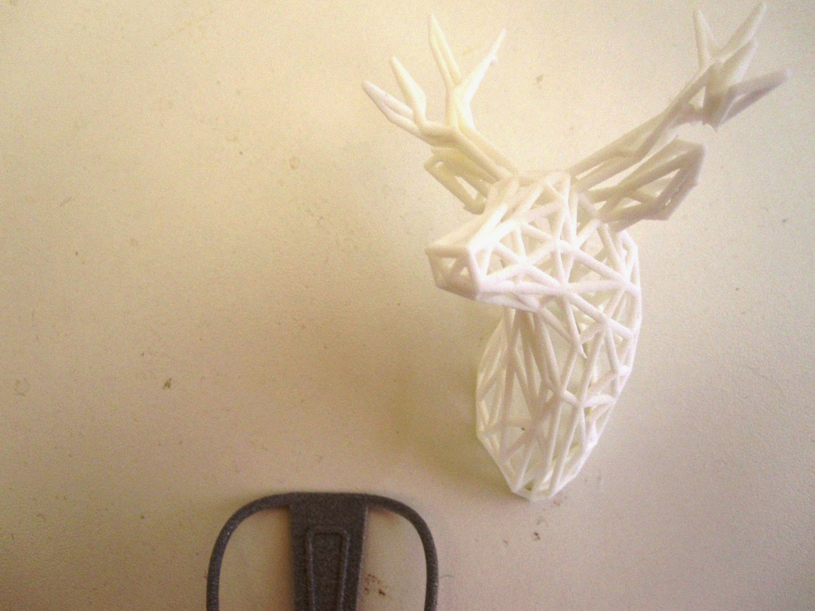 Modern dolls' house miniature 3D-printed cafe chair next to three 3D-printed stag head.