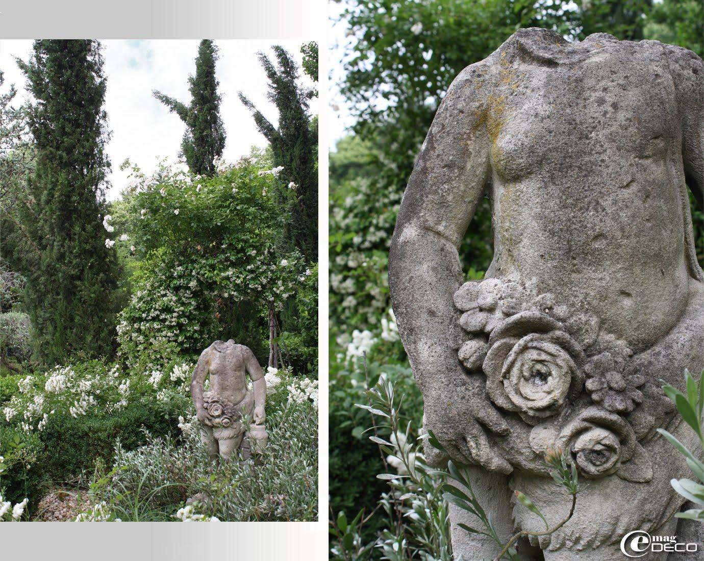 Au milieu d'un jardin planté de rosiers en buissons hirsutes ou grimpants, un vieux putti en pierre