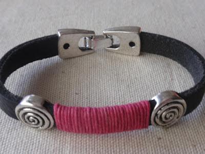 Pulsera chico en cuero negro con adornos plateados e hilo rosa fuerte