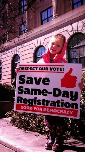 "Young CUCC member holds ""Save Same-Day Registration"" sign at 2013 HKonJ"