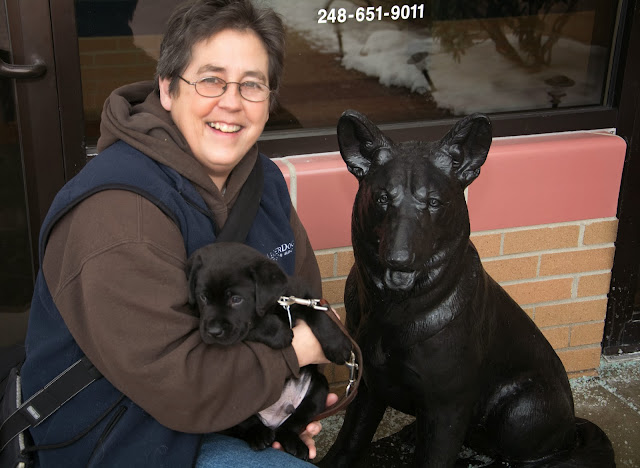 The woman with glasses and short dark hair is kneeling next to a black statue of a German Shepherd dog. She is holding a small black lab puppy in her arms.
