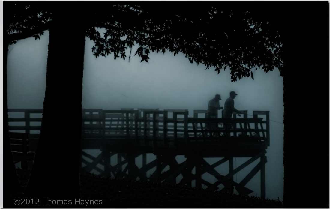 Fishermen on a river pier, seen trhrough dense morning fog