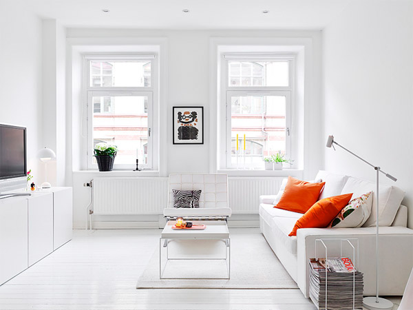 The Living Room Opens With All White Surfaces Energized Colorftul Details Such As Orange Pillows Small