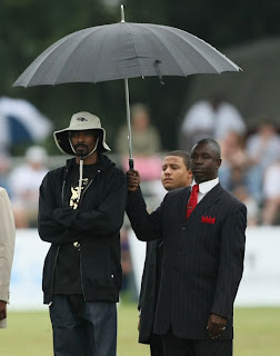 funny picture: snoop dogg servant carry the umbrella