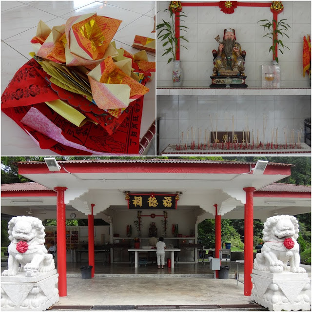 Paying respect to The City God or Cheng Huang with joss paper and joss sticks, who guards against earthquakes and other disasters at the entrance of Chinese Cemetery in Ipoh, Perak,  Malaysia