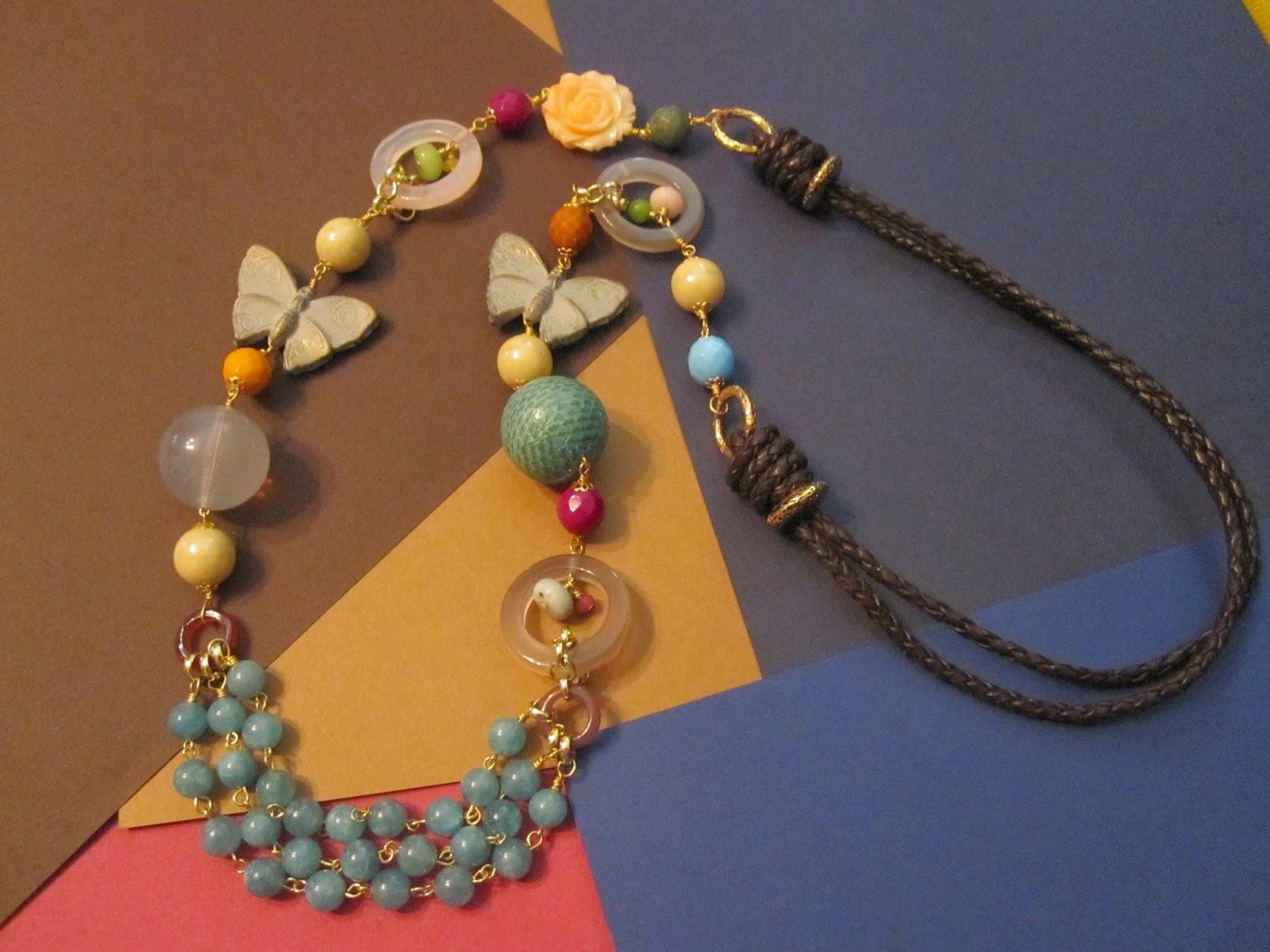 Collar largo en dorado con dos mariposas de madera pintadas, una rosa de  resina, 3 aros de piedra en gris y rosa, cuentas perladas y facetadas de  colores