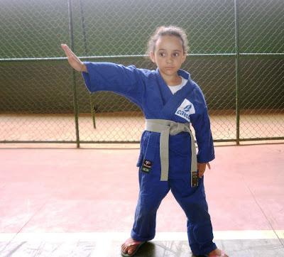 Início da descrição da imagem... Foto da Laura, de 5 anos de idade, vestida de kimono azul, com a faixa cinza, com a mão direita estendida, como se estivesse cortando o ar, demonstrando a técnica Naname Uê Uchi. Fim da descrição da imagem. Início da legenda...