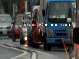 Japanese trucks wait in traffic copyright peter hanami 2013