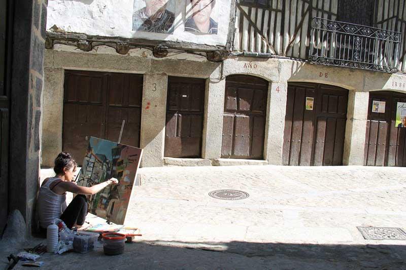 una pintora joven sentada en el suelo pinta unade las calles de Mogarraz