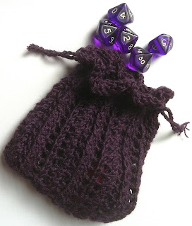 A photograph of a purple knitted lace bag with purple dice spilling out of the top