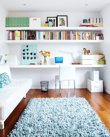 Floating wall length shelves in a home office with hardwood floor, a light blue shag rug and a white sofa
