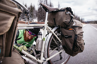 scraping ice off the pedals of a soma grand randonneur bicycle while crossing the continental divide in wyoming