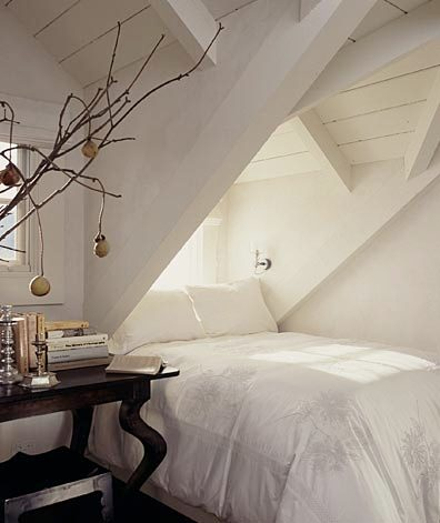 white attic bedroom with exposed beams and a dark wood side table