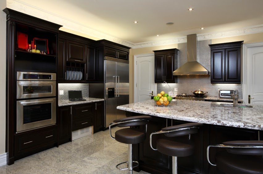 kitchen with dark toned wood cabinetry and light marble surfaces