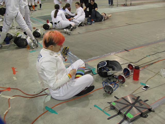 A fencer sits on the floor