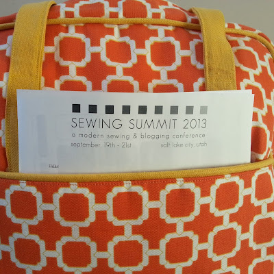 an orange geometric bag with papers in the pocket