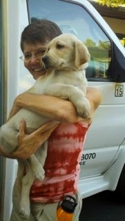 A very young Gucci puppy (yellow Lab) is held by her smiling new raising at the Puppy Truck delivery