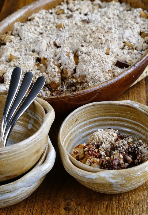 An dish full of a sweet crumble and serving bowls