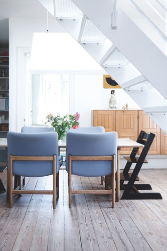Dining room in a Danish home with blue chairs and stained wood cabinets