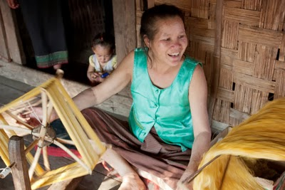 This Lao village artisan, whose silk work supplements her subsistence farming activities, twists the silk yarns to condition and strengthen them prior to weaving.
