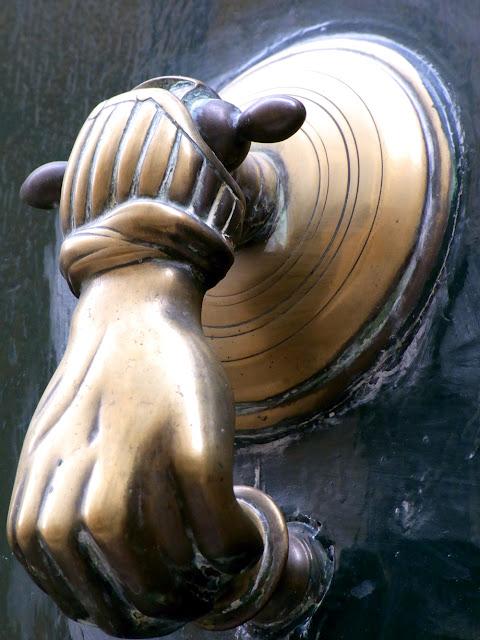 Alter Messing Türklopfer geformt als Hand, an einer französischen Holztür, Provence