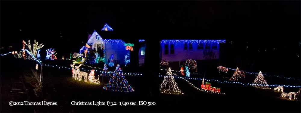 House with christmas lights adorning home and yard; the home is lit in blue
