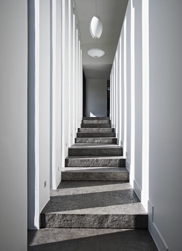 Picture of concrete staircase in the hallway with white walls and floor to ceiling windows