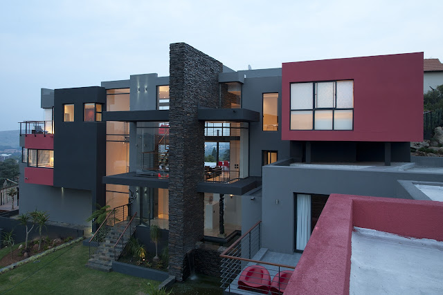 Picture of modern Lam House with grey and red facade as seen from the roof of the garage