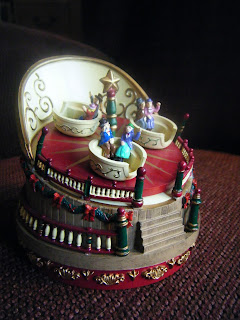 a small, brightly-painted music box in the shape of a whirling carnival ride; the tiny people in it are dressed in Victorian style