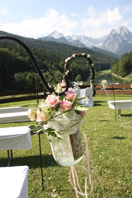 Gartenstecker mit Blumen-gefüllten Gläsern für eine Hochzeit im Freien
