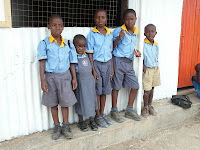 Children standing in front of Kasese Humanist Primary School in Uganda.