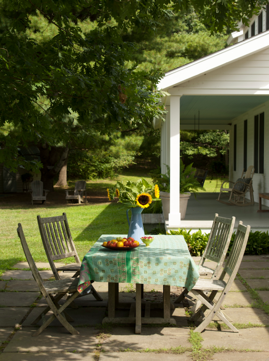 country farmhouse dining al fresco with sunflowers, flag stone patio
