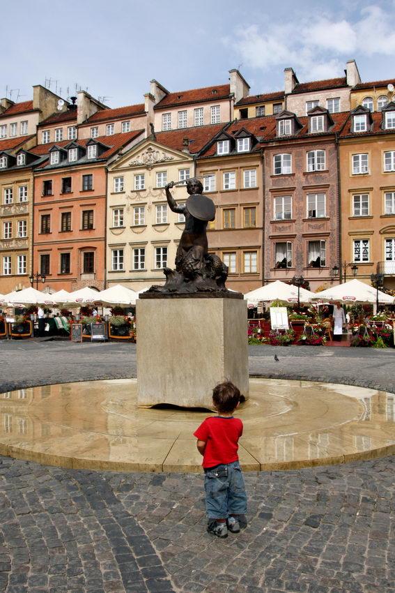 Foto na praça com a estátua da sereia no centro da imagem e uma criança, de costas,  a olhar para ela